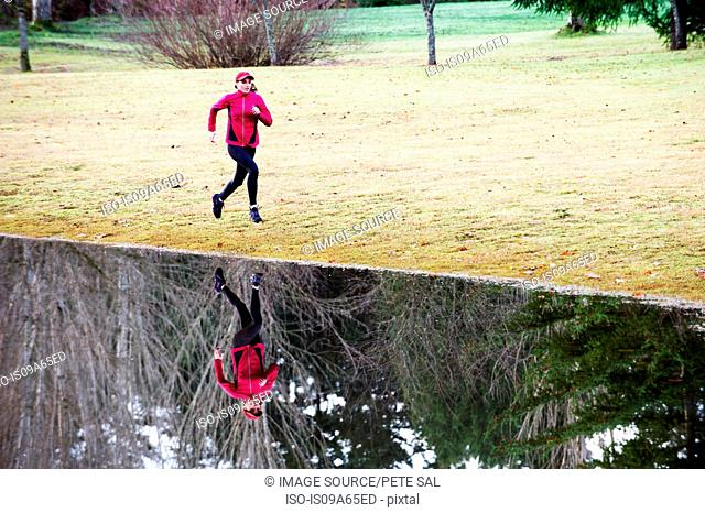 Woman running by still rural lake