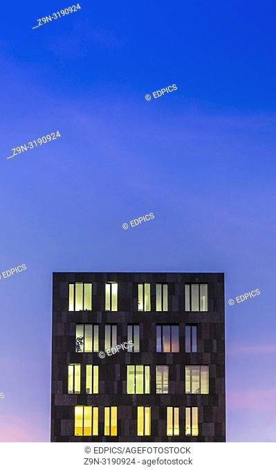 modern office building at dusk against blue evening sky, stuttgart, baden-wuerttemberg, germany