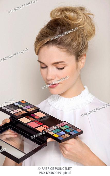 Beautiful woman looking at eye shadow palette