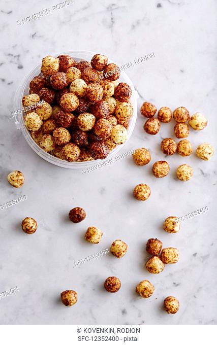 Corn pops in a plastic tub and on a marble background