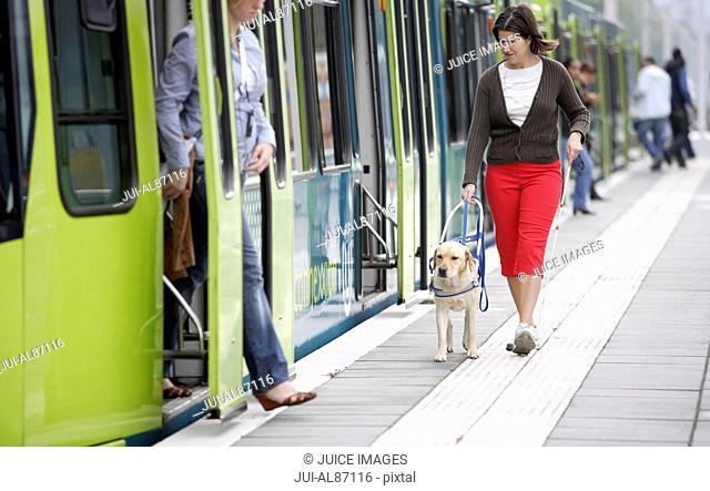 Blind woman and seeing eye dog at train station