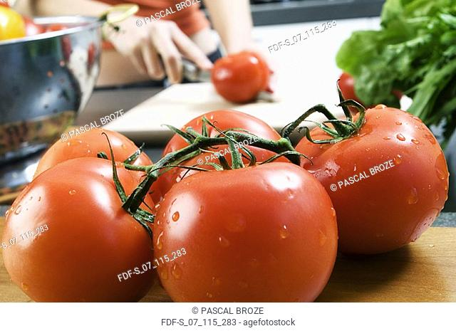 Close-up of five tomatoes with a woman cutting a tomato in the background