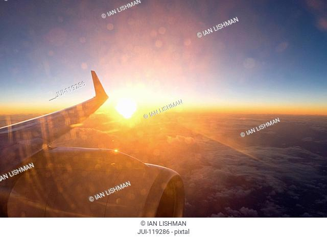 Sunset view through window over the wing and jet engine of a passenger plane
