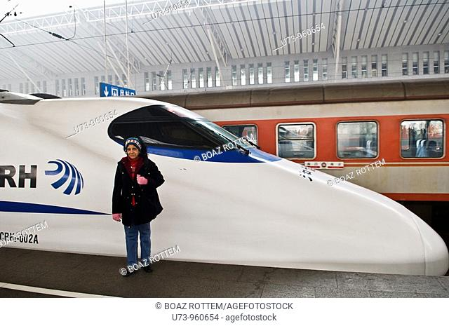A foreign tourist next to the super modern CRH train in China