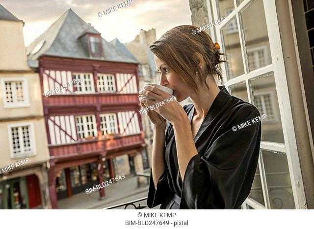 Caucasian woman drinking coffee on balcony in city