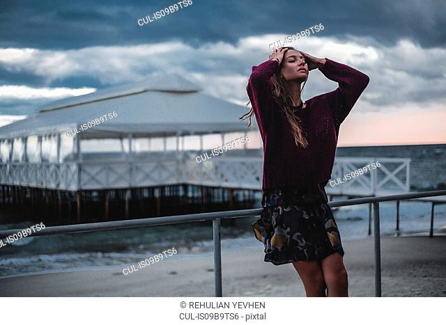 Young woman with hands in long hair leaning against beach pier at dusk, Odessa Oblast, Ukraine