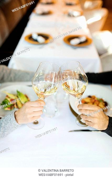 Close-up of couple clinking wine glasses in a restaurant
