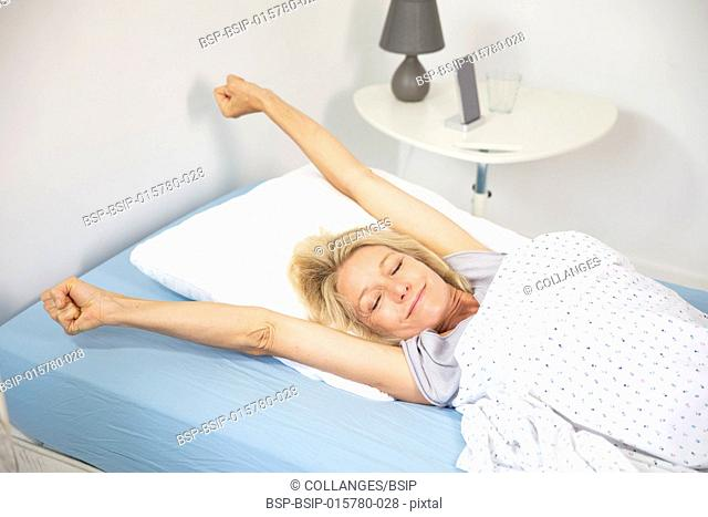 Woman waking up in her bed and stretching