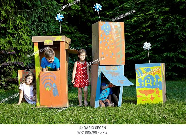 Children playing in cardboard boxes, Munich, Bavaria, Germany