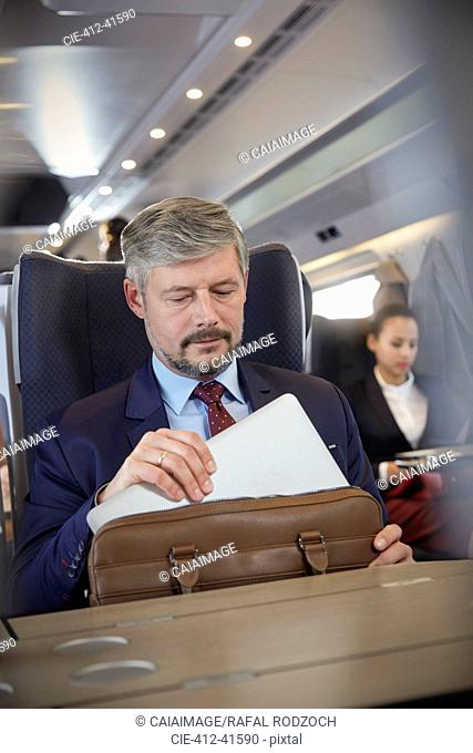 Businessman removing laptop from briefcase on passenger train