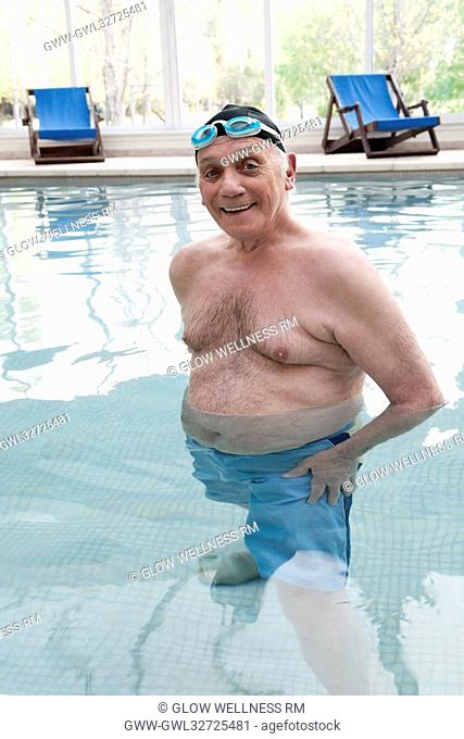 Portrait of a man standing and smiling in a swimming pool