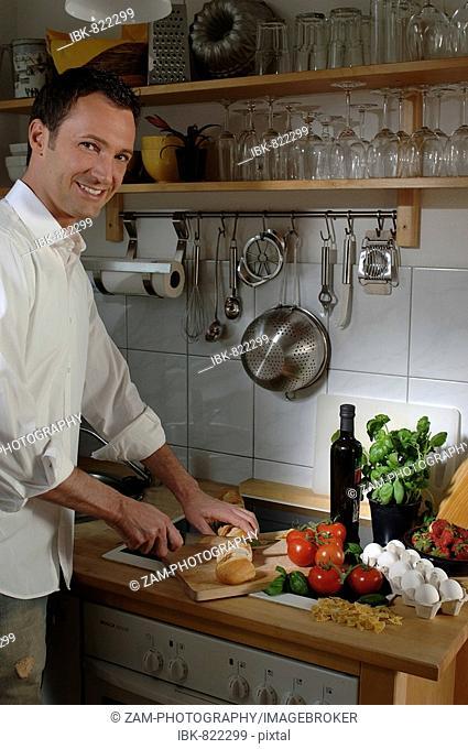 31-year-old man cooking Italian food, cutting bread