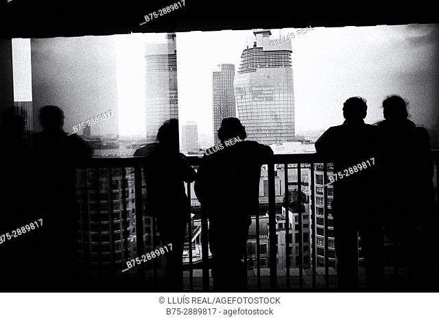Silhouettes of unrecognizable people looking at the City from a balcony. Tate Modern, The City, Bankside, London, UK
