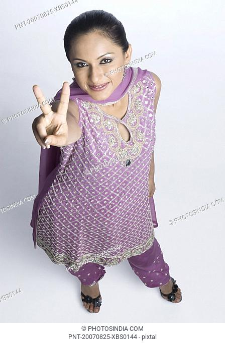 High angle view of a mid adult woman in salwar kameez and making a peace sign