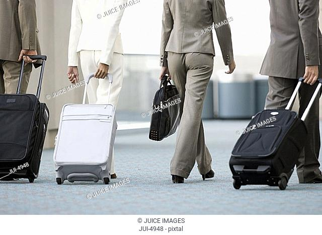Four business colleagues walking in airport with luggage, low section, rear view