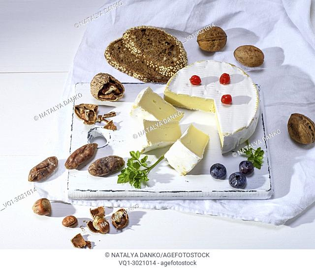 round Camembert cheese on a white wooden board, next to sausage and nuts, white wooden table, top view, empty space