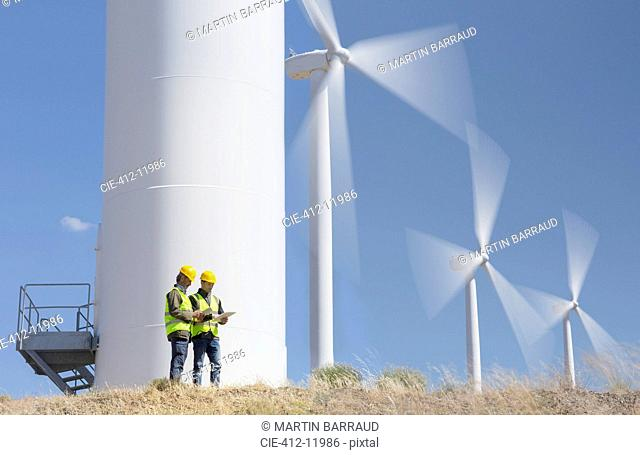 Workers talking by wind turbines in rural landscape
