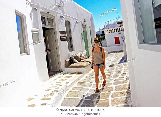 Young adult woman walking the streets of Mykonos, Greek Islands, Greece