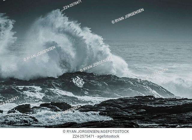 Dark atmospheric storm scene of big waves breaking a stone shoreline during turbulent weather conditions. Granville Harbour, Tasmania, Australia