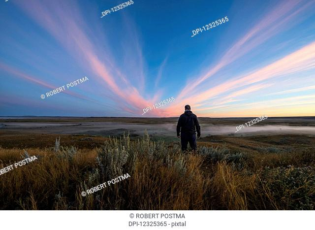 A man stands watching watching the sunrise colour over the Frenchman River Valley in Grasslands National Park; Saskatchewan, Canada