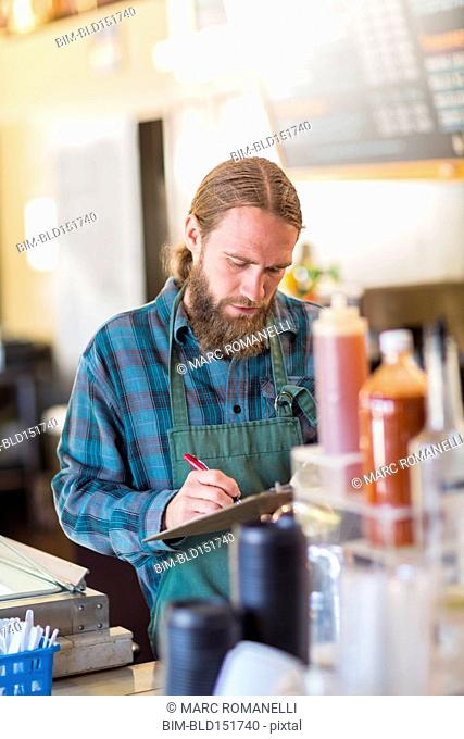 Caucasian server writing on clipboard in cafe