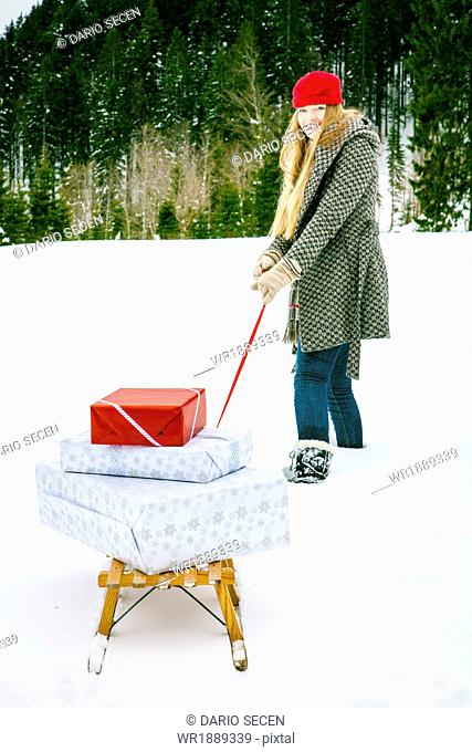 Woman Pulling Gifts On Sled, Spitzingsee, Bavaria, Germany