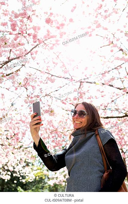 Mature woman taking smartphone selfie in front of cherry blossom