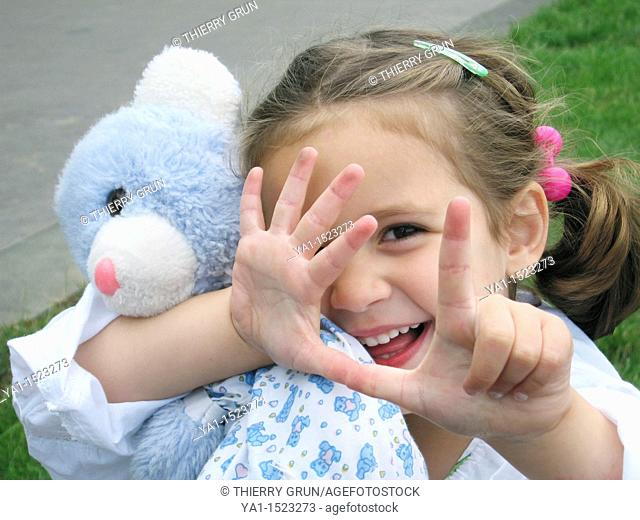 Young girl hugging her teddy bear and counting with fingers