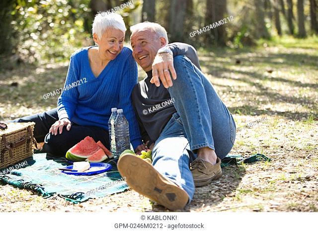 Senior couple having picnic in garden, smiling