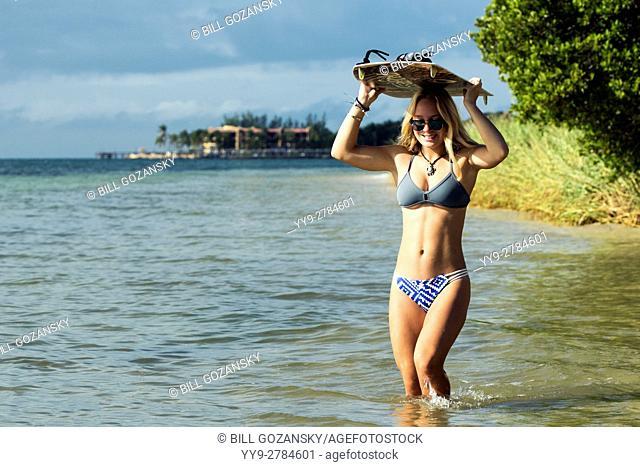 Teenage Girl walking with Kiteboard at Coco Plum Beach - Marathon, Florida, USA