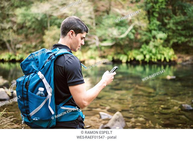 Hiker looking on smartphone in nature