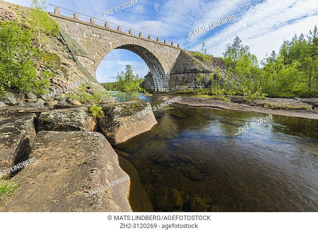 Old railroad bridge made of bricks with a portal, running water from river under it and forest in background, Jokkmokk county, Swedish Lapland, Sweden