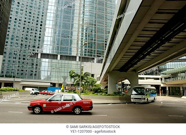 Red taxicab driving past modern skyscrapers, Hong Kong Island, Hong Kong, China