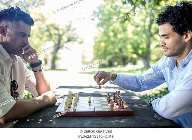 Two men playing game of chess in park