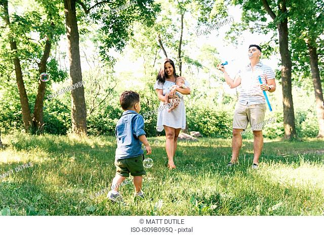 Parents blowing bubbles with toddler and baby son in Pelham Bay Park, Bronx, New York, USA