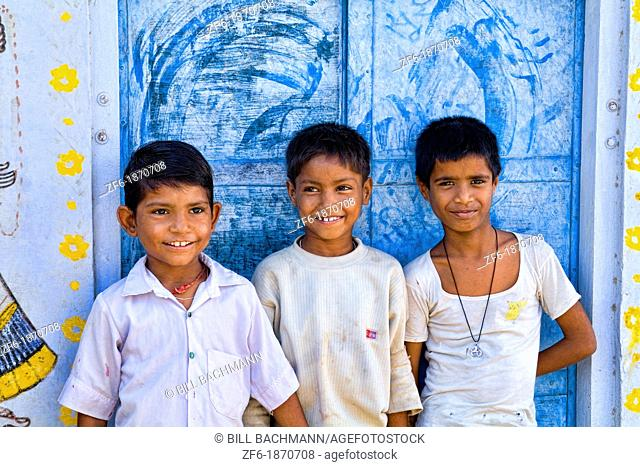 Colorful children aged 6 and 7 against blue wall portrait in Jaipur Rajasthan India