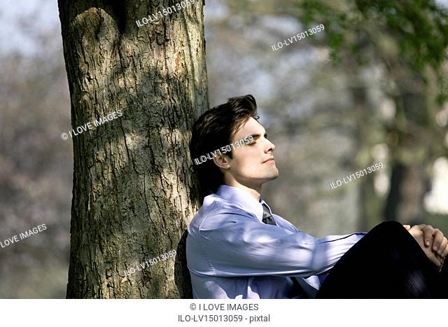 A businessman leaning against a tree, resting