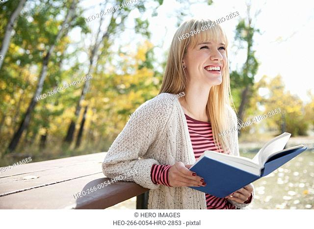 Young woman with book at the park