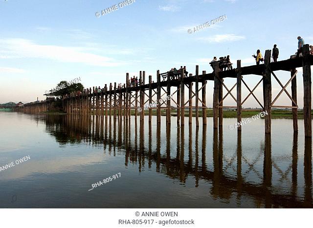 People crossing U Bein's Bridge, supported by 984 teak posts over 1.2 km distance across Thaumthaman Lake, Mandalay, Myanmar (Burma), Asia