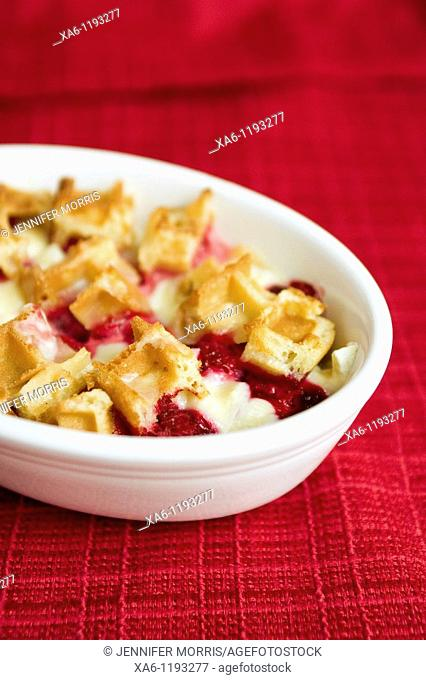 Waffle and raspberry baked pudding in a white dish