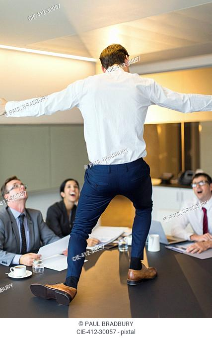 Surprised colleagues watching exuberant businessman dancing on conference table