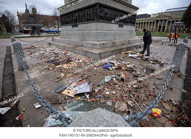 01 January 2019, Baden-Wuerttemberg, Stuttgart: An employee of a cleaning company sweeps up fireworks and other remains of New Year's Eve on the Schlossplatz