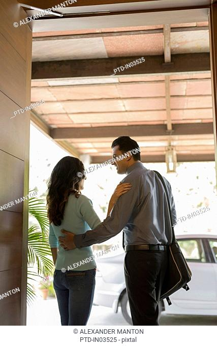 India, Woman saying goodbye to man at front door