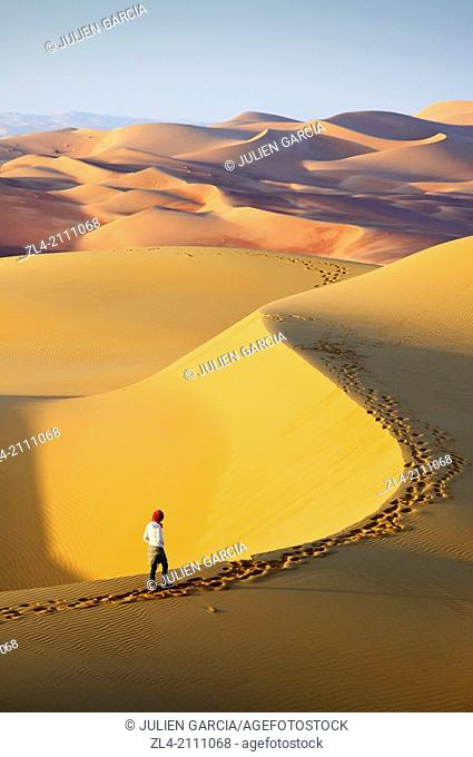 Woman in the sand dunes of the empty quarter desert. United Arab Emirates, UAE, Abu Dhabi, Liwa Oasis, Moreeb Hill, Tal Mireb. Model Released