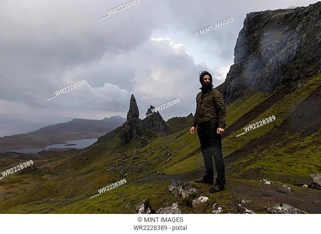 A man on a narrow path rising to a dramatic landscape of rock pinnacles under an overcast sky with low cloud