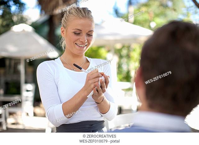 Smiling waitress writing ordering on notepad