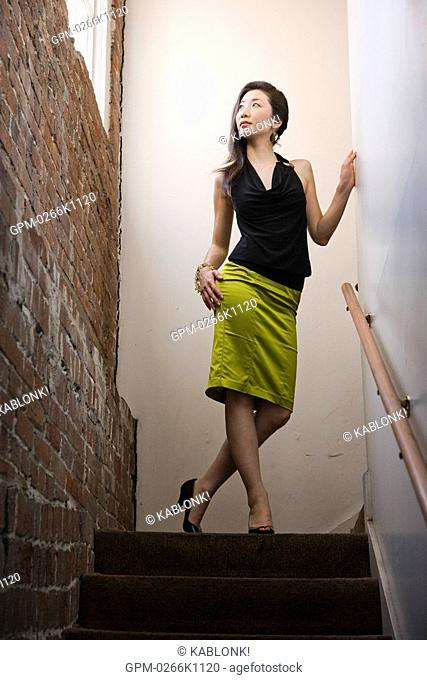 Portrait of young stylish Asian woman standing on top of stairs looking out window