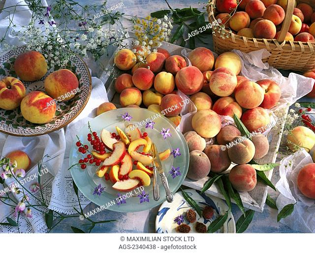 Agriculture - Still life of yellow and white flesh peaches in bowls and a wooden container with sliced peaches on a glass plate, studio