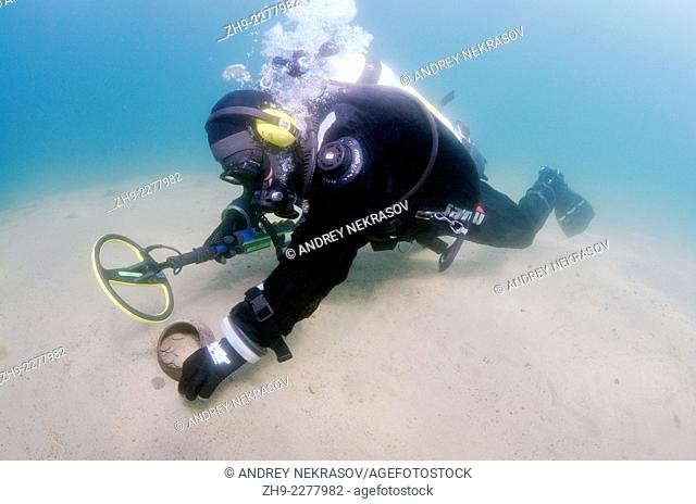 Diver with the metal detector found a pot with antique coins, lake Baikal, Siberia, Russia, Eurasia