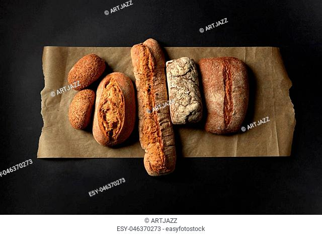 Different kinds of loafs represented on baking paper over black background. Baking and cooking concept background